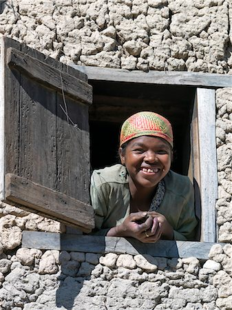A girl wearing a Malagasy woven hat peeps out of the upstairs window of her home near Ambalavao,Madagascar Stock Photo - Rights-Managed, Code: 862-03364011
