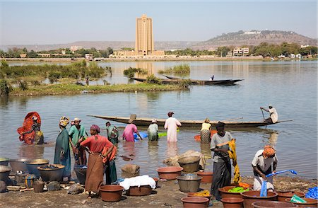 dyed - Mali,Bamako. Dyeing and rinsing cotton cloth on the outskirts of Bamako with the imposing Bank of West Africa building dominating the skyline on the opposite bank of the Niger River. Stock Photo - Rights-Managed, Code: 862-03364119