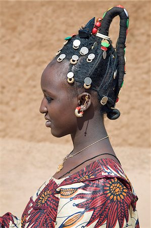 Mali,Gao. A Songhay woman at Gao market with an elaborate coiffure typical of her tribe. The silver coins are old French francs and British West Africa coins dating back one hundred years. Stock Photo - Rights-Managed, Code: 862-03364172