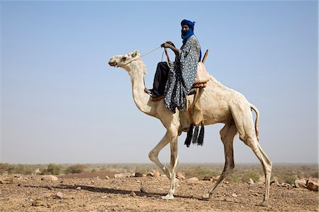 desert people dress photos - Mali,Timbuktu. A proud Tuareg rides his camel across semi-desert stony terrain near Timbuktu. Stock Photo - Rights-Managed, Code: 862-03364234