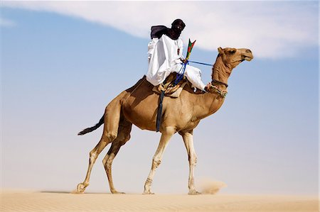 desert people dress photos - Mali,Timbuktu. In the desert north of Timbuktu,a Tuareg man rides his camel across a sand dune He steers the animal with his feet. Stock Photo - Rights-Managed, Code: 862-03364257