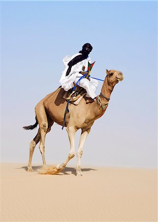 desert people dress photos - Mali,Timbuktu. In the desert north of Timbuktu,a Tuareg man rides his camel across a sand dune. He steers the animal with his feet. Stock Photo - Rights-Managed, Code: 862-03364258
