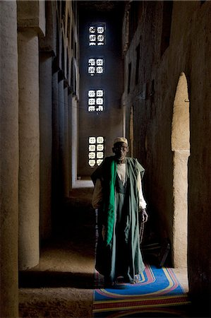 Mali,Niger Inland Delta. The imam of Kotaka pauses beside an archway inside the impressive Sudan-style mosque which dominates Kotaka village on the banks of the Niger River. Stock Photo - Rights-Managed, Code: 862-03364267