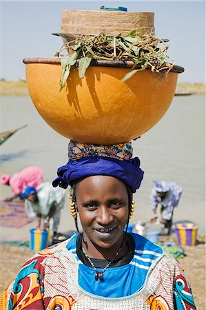 Mali,Tupe,Niger Inland Delta. A woman with gold hair ornaments leaves the Niger River with a headload of cooking pots and utensils. Her facial markings and the light tattooing round her lips indicate that she is from the Peul tribe. Stock Photo - Rights-Managed, Code: 862-03364284