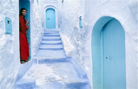 A local woman steps out into the whitewashed streets of the Rif Mountains town of Chefchaouen. The distinctive white and blue colour scheme was first introduced by Jewish refugees fleeing Spain in the 15th century. Stock Photo - Rights-Managed, Code: 862-03364804