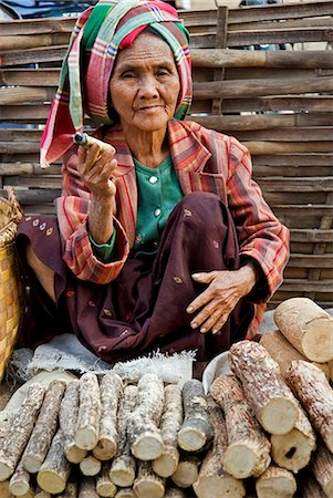 Myanmar. Burma. Nyaung U. An old woman smokes a local cheroot as she sells thanahka - the bark of Lemonira acidissimo tree ground to a paste with water for use as sunscreen. Stock Photo - Rights-Managed, Code: 862-03365095
