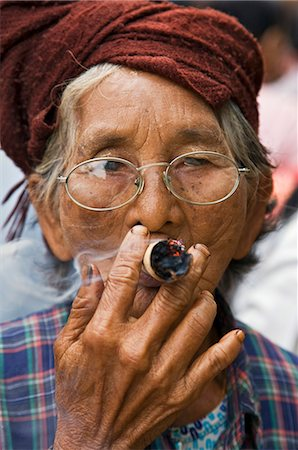 Myanmar. Burma. Nyaung U. An old bespectacled woman smokes a local cheroot in Nyaung U market. Stock Photo - Rights-Managed, Code: 862-03365097