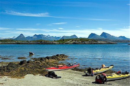 Norway,Nordland,Helgeland. Sea kayaking down the coast of Norway in the summer - a group of kayaks pulled up on the beach with a range of mountains in the background Stock Photo - Rights-Managed, Code: 862-03365667
