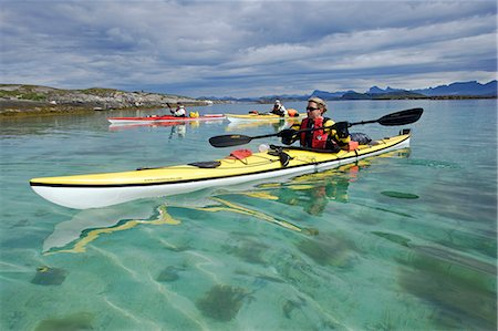 Norway,Nordland,Helgeland. Summer water sports in Norway - sea kayaking down up the coast of Norway with cystal clear waters and mountains in the background. Stock Photo - Rights-Managed, Code: 862-03365680