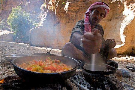 Jordan,Petra,Wadi Daphna. A local beduin guide dressed in traditional clothing prepares a lunch time meal over an open fire in the dead chasm within Wadi Daphna. Stock Photo - Rights-Managed, Code: 862-03365943