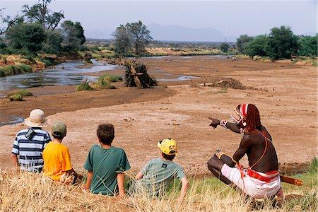 A Samburu warrior talks to children about the bush on a Cheli & Peacock family safari. Stock Photo - Rights-Managed, Code: 862-03365967