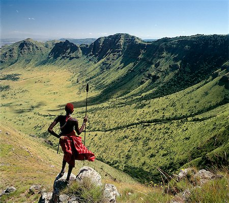A Samburu warrior looks out across the eastern scarp of Africa's Great Rift Valley at Poro,Northern Kenya where the land drop precipitously 3,000 feet. Stock Photo - Rights-Managed, Code: 862-03366016