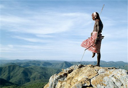 A Samburu warrior stands sentinel over a vast tract of unspoilt,semi-arid bush scrub country. The poor pasture here is an important resource for the pastoral Samburu people. Stock Photo - Rights-Managed, Code: 862-03366018