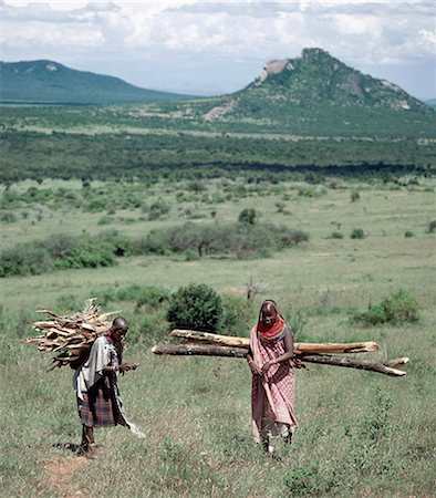 Samburu women are responsible for collecting firewood and carrying it to their homes. Supported by leather straps over their foreheads,the loads they carry would make most strong men groan under the weight Fire is a potent symbol of life; the fire in the hearth of a Samburu house must never be allowed to die out. Stock Photo - Rights-Managed, Code: 862-03366029