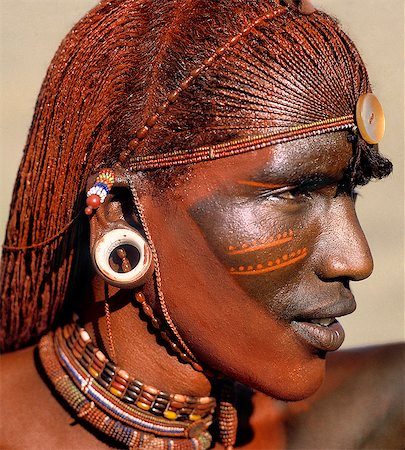A Samburu warrior resplendent with long,braided,Ochred hair. The round ear ornaments of the warriors are fashioned from ivory. Samburu warriors are vain and proud,taking great trouble over their appearance. Ochre is a natural earth containing ferric oxide which is mixed with animal fat to the consistency of greasepaint. Stock Photo - Rights-Managed, Code: 862-03366036