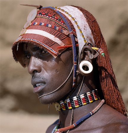 A Samburu warrior resplendent with long,braided,Ochred hair. The braids at the front have been fashioned in a protruding fringe rather like a sunshade. The cloth on top keeps the braids in place. The round ear ornaments of the warriors are made of ivory. Samburu warriors are vain and proud,taking great trouble over their appearance. Stock Photo - Rights-Managed, Code: 862-03366037