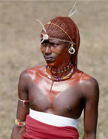 A Samburu warrior resplendent with his long braids of Ochred hair. His round ear ornaments are made of ivory. Samburu warriors are vain and proud,taking great trouble over their appearance. They use ochre extensively; it is a natural earth containing ferric oxide which is mixed with animal fat to the consistency of greasepaint. Stock Photo - Rights-Managed, Code: 862-03366038