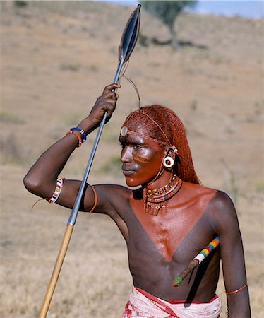A Samburu warrior resplendent with long braids of Ochred hair. His round ear ornaments are made of ivory. Samburu warriors are vain and proud,taking great trouble over their appearance. They use ochre extensively; it is a natural earth containing ferric oxide which is mixed with animal fat to the consistency of greasepaint. By tradition,warriors always used to carry two spears. Stock Photo - Rights-Managed, Code: 862-03366039