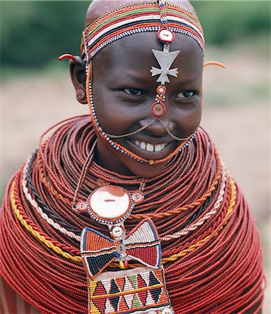 Samburu girls are given strings of beads by their fathers when they are still young. As soon as they are old enough to have lovers from the warrior age-set,they regularly receive gifts from them. Over a period of years,their necklaces can smother them up to their necks. The metal cross-like ornament hanging from the girl's headband has no religious significance. Stock Photo - Rights-Managed, Code: 862-03366046