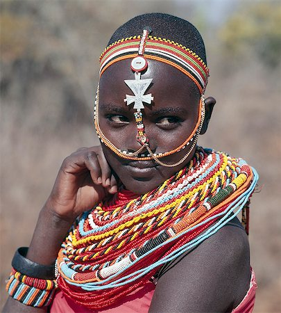 Samburu girls are given strings of beads by their fathers when they are still young. As soon as they are old enough to have lovers from the warrior age-set,they regularly receive gifts from them. Over a period of years,their necklaces can smother them up to their necks. The metal cross-like ornament hanging from the girl's headband has no religious significance. Stock Photo - Rights-Managed, Code: 862-03366047