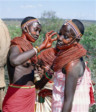 Samburu girls paint each others faces with abstract designs in readiness for a dance. Already,their necks and beaded necklaces have been coated with red ochre. Only girls and warriors decorate their faces; the orange powder they use is called blue. Stock Photo - Rights-Managed, Code: 862-03366049