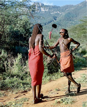 Two Samburu warriors converse,their long braids of Ochred hair distinguishing them from other members of their society. Samburu warriors are vain and proud,taking great trouble over their appearance. An ostrich feather pompom decorates the top of a spear. Stock Photo - Rights-Managed, Code: 862-03366040