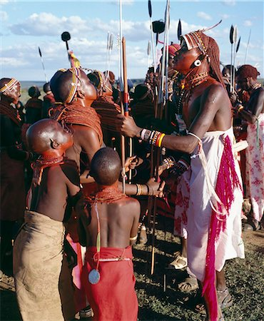During Samburu wedding celebrations,warriors resplendent with long Ochred braids dance with young girls who have put on all their finery for the occasion. Both warriors and girls smear their faces,necks and shoulders with red ochre mixed with animal fat to enhance their appearance. Two spears are tipped with ostrich-feather pompoms. Stock Photo - Rights-Managed, Code: 862-03366058