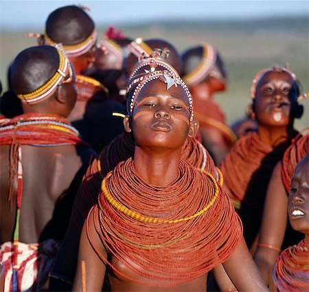Young Samburu girls dance during a wedding celebration. By arching their backs and thrusting out their chests,they flick their beaded necklaces up and down while dancing silently to the songs of the warriors. Their bodies and necklaces have been smeared with red ochre. Stock Photo - Rights-Managed, Code: 862-03366050