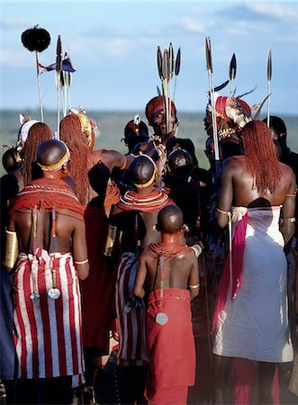 Kenya,Maralal,Lodokejek. Samburu warriors and young girls sing and dance during a wedding celebration. The long Ochred braids of the warriors distinguish them from other members of Samburu society. A black ostrich-feather pompom decorates the top of a spear. Stock Photo - Rights-Managed, Code: 862-03366052