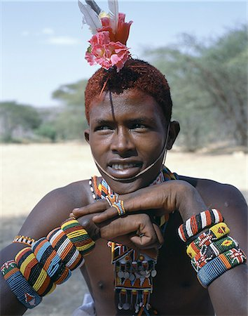 The adornments of Samburu warriors change from generation to generation. In the 1990's cheap plastic flowers from China became fashionable. This warrior is wearing several bracelets,which bear the Kenyan coat of arms. Stock Photo - Rights-Managed, Code: 862-03366063