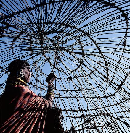 A Turkana woman makes the final ties to the dome-shaped framework of her home. In wet weather,hides will be laid on top and secured with leather thongs. Stock Photo - Rights-Managed, Code: 862-03366098