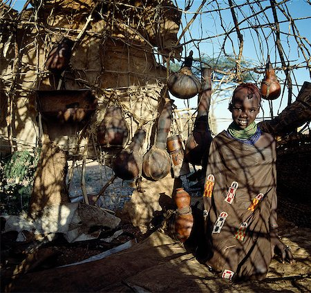 Almost everything a Turkana family owns is kept in a wife's day hut. Wooden containers,gourds,utensils and personal clothing or ornaments hang from the ceiling or walls. Watering troughs,donkeys panniers and a grinding stone lean against the walls. The wife's eldest daughter will look after the home during the day while being nanny to her younger brothers and sisters. Stock Photo - Rights-Managed, Code: 862-03366099