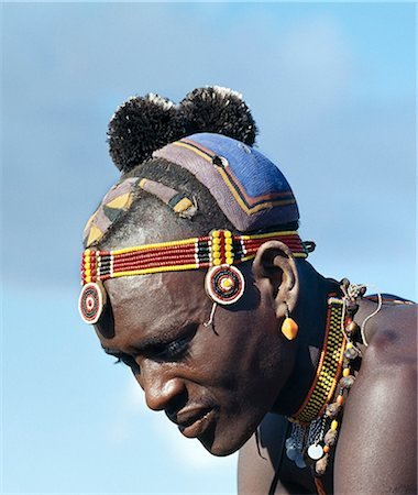 A Turkana man with a fine clay hairstyle,so typical of the southern Turkana. The black ostrich feather pompoms denote that the man belongs to the ng'imor (black) moiety of his tribe. Stock Photo - Rights-Managed, Code: 862-03366105