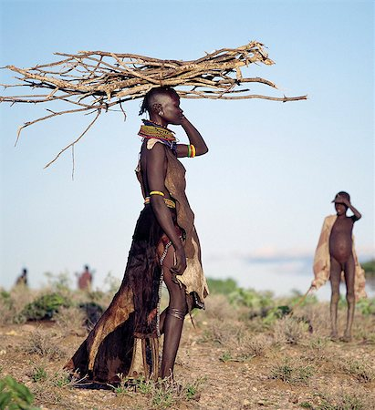 In the semi-arid terrain of Turkanaland,women have to travel great distances to collect firewood. Like other Nilotic people,Turkana women balance heavy loads on their heads with graceful carriage and poise. The attire of this woman is typical of married women in the tribe. Stock Photo - Rights-Managed, Code: 862-03366108