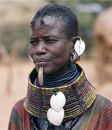 A Turkana woman wears all the finery of her tribe: brass lip plug,beaded collar decorated with bleached shells of the African land snail,leaf-like ear ornaments and metal earrings from which hang tiny rings of goat horn. Stock Photo - Rights-Managed, Code: 862-03366109