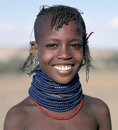 A pretty young Turkana girl has already had the flesh below her lower lip pierced in readiness for a brass ornament after her marriage. The rims of her ears have also been pierced and the holes kept open with small wooden sticks. Stock Photo - Rights-Managed, Code: 862-03366114