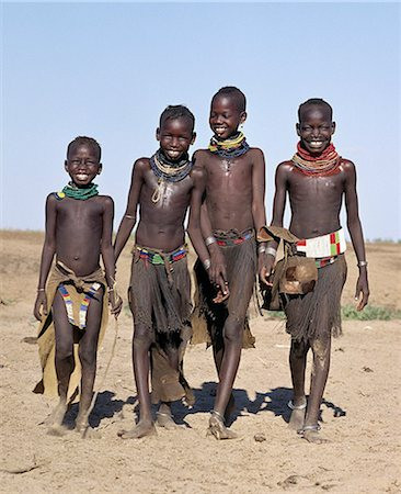 A jovial group of Turkana girls in traditional attire. Their aprons are made of goatskin,either beaded or cut into thin strips before braiding. The two girls in the middle have already had the flesh below their lower lips pierced in readiness for a brass ornament after marriage. Stock Photo - Rights-Managed, Code: 862-03366115
