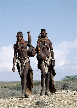 Two Turkana girls set off to fetch water from a nearby Waterhole. Their water containers are made of wood by the women of the tribe. Their 'V' shaped aprons are made of goatskin and have been edged with hundreds and hundreds of round discs fashioned out of ostrich eggshells. Stock Photo - Rights-Managed, Code: 862-03366116