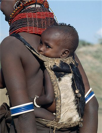 When a Turkana woman gives birth,four goats will be slaughtered in a twenty-four-hour period to celebrate the occasion. The skin of the first goat will be made into a pouch for carrying the baby on its mother's back. The small wooden balls on the back of this pouch are charms to ward off evil spirits. The baby is wearing a bracelet of ostrich eggshell beads. Stock Photo - Rights-Managed, Code: 862-03366118