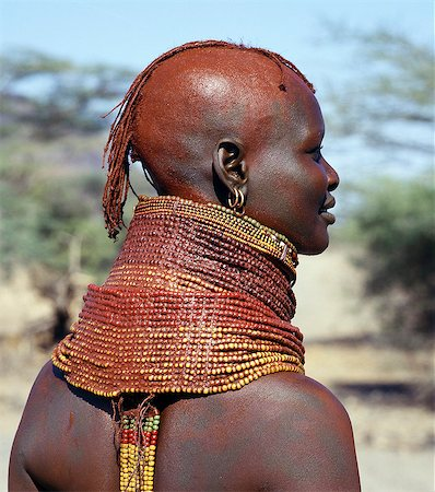 A Turkana girl's necklaces are well-oiled with animal fat and glisten in the sun. The use of red ochre has been copied from their Samburu neighbours and is not widespread. Occasionally,a girl will put on so many necklaces that her vertebrae stretch and her neck muscles gradually weaken. The partially shaven head is typical of Turkana women and girls. Stock Photo - Rights-Managed, Code: 862-03366110