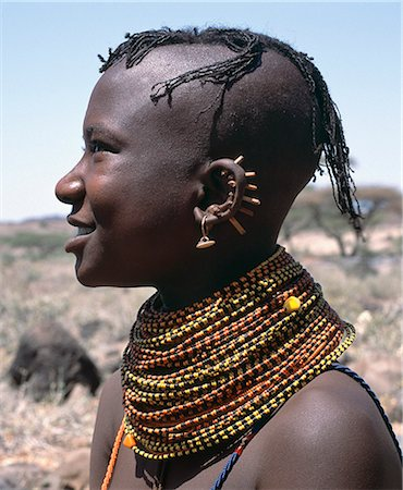 A young Turkana girl has had the rims of her ears pierced in seven places and keeps the holes open with small wooden sticks. After marriage,she will hang leaf-shaped metal pendants from each hole. Stock Photo - Rights-Managed, Code: 862-03366112