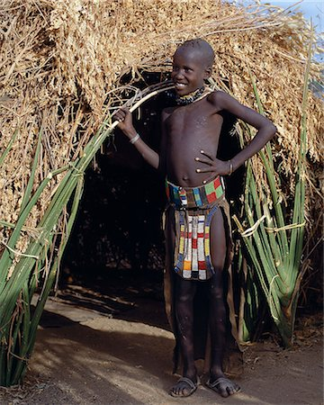 A young Turkana girl wearing an attractively beaded leather apron and belt stands outside her mother's home. Sansevieria or wild sisal lines the lower walls of the house. Cicatrization round the nipples of a girl is not an uncommon form of beautification. Stock Photo - Rights-Managed, Code: 862-03366127