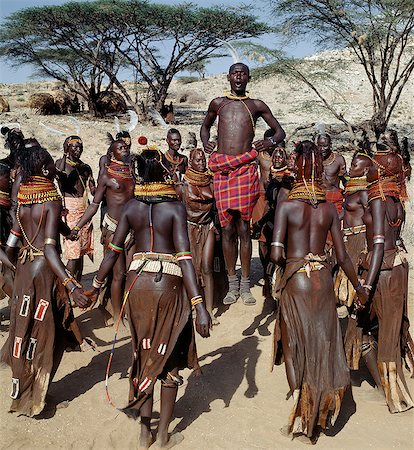 Song is an art form ingrained in Turkana culture. At the end of a dance session,the participants invariably enjoy the Song of the Bulls. Each young man will take centre-stage to extol the praises of his favourite ox. He will explain how it came into his possession,its distinguishing traits and with outstretched arms,imitate the shape of its horns. Stock Photo - Rights-Managed, Code: 862-03366134
