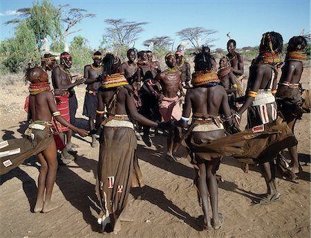 Song is an art form ingrained in Turkana culture. At the end of a dance session,the participants invariably enjoy the Song of the Bulls. Each young man will take centre-stage to extol the praises of his favourite ox. He will explain how it came into his possession,its distinguishing traits and with outstretched arms,imitate the shape of its horns. Stock Photo - Rights-Managed, Code: 862-03366132