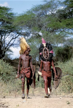 Kenya,Kajiado,lpartimaro. Two Maasai warriors in full regalia. The headress of the man on the left is made from the mane of a lion while the one on the right is fringed with black ostrich feathers. Their traditional weaponry includes long-bladed spears and shields are made of buffalo hide. Stock Photo - Rights-Managed, Code: 862-03366146