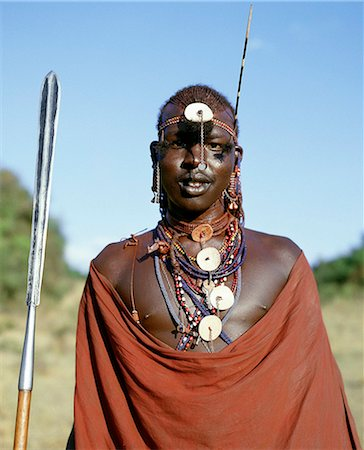 A Maasai warrior in full regalia. He has stuck a porcupine quill in his beaded headband to add to his other decorations. His long,Ochred plaits have been drawn forward from the crown of his head and tied in three bunches. Stock Photo - Rights-Managed, Code: 862-03366148