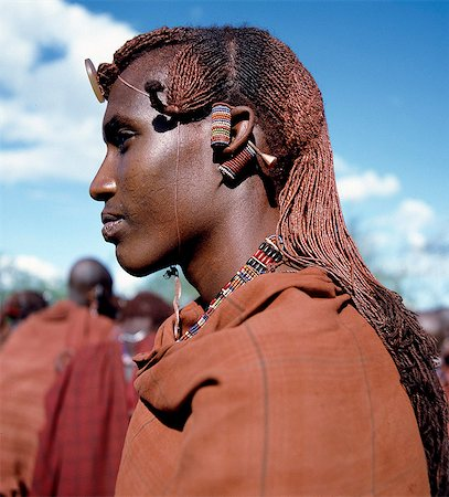 Kenya,Kajiado,Maparasha. A Maasai warrior resplendent with long,ochred braids. This singular form of hairstyle distinguishes warriors from the rest of their society. This man has looped his elongated and decorated earlobes over his ears - a common practice when walking through thorn scrub country to prevent the loops being snagged by thorns. Stock Photo - Rights-Managed, Code: 862-03366149