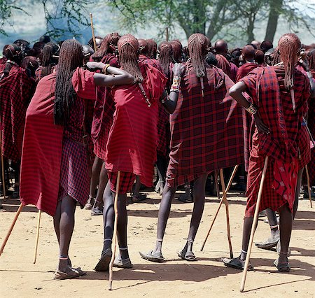 Maasai warriors resplendent with long ochred braids relax and wait for the start of a ceremony. Red has always been their preferred colour. Stock Photo - Rights-Managed, Code: 862-03366143