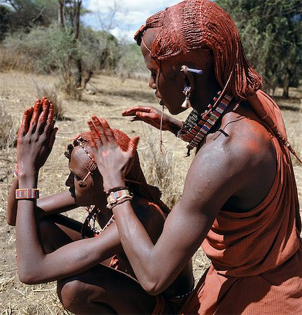 A Maasai warrior resplendent with long ochred braids tied in a pigtail at the back,puts red ochre on his friend's plaits. Red ochre is anatural earth,which is mixed with animal fat to the consistency of greasepaint. Stock Photo - Rights-Managed, Code: 862-03366156