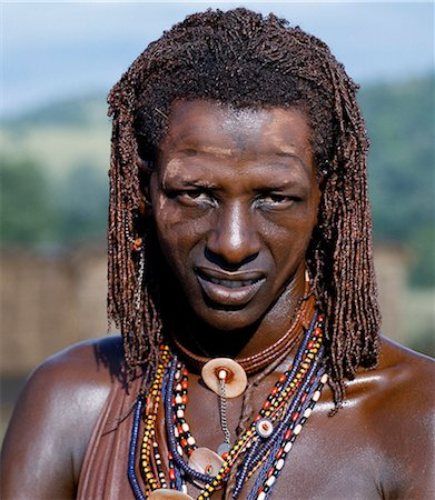 A Maasai warrior resplendent with long ochred braids. His body has been smeared with red ochre mixed with animal fat while parts of his face have been covered with ochre powder. Stock Photo - Rights-Managed, Code: 862-03366150